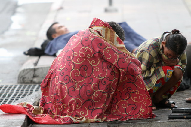 Homeless People On A Street Bury Themselves Under Clothes To Rug Up Against  Cold Weather.