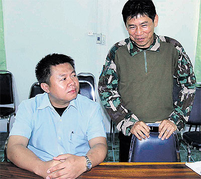 Suriyon Pothibandit, left, assistant to Kaeng Krachan National Park chief Chaiwat Limlikitauksorn, right, surrenders to police, who want him in connection with the recent burning of a wild elephant carcass in the park.