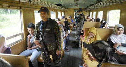 Armed officers provide security on board Train No.006 bound for Narathiwat's Sungai Kolok district in late November.