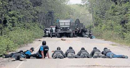 Police officers and soldiers take up position during a search for explosives in Ban Raman after local farmers alerted them to suspicious activities in Yala province Tuesday. REUTERS