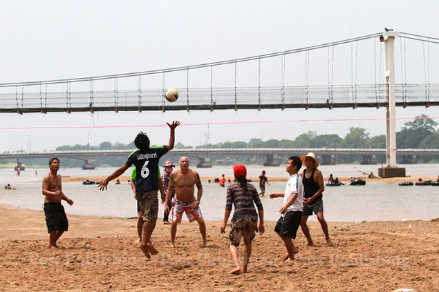 A group of locals enjoy a game of volleyball on the waterbed of the dried out Ping River in Tak province.