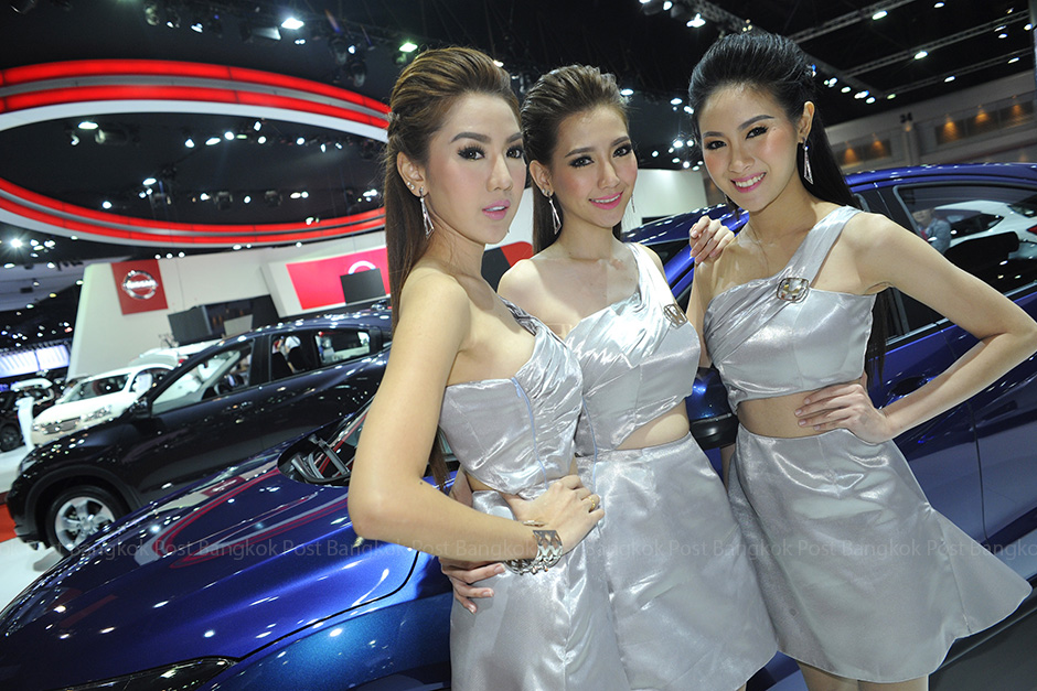 Visitors look at cars and motorcycles displayed at the 36th Bangkok International Motor Show, as models pose for photos. The world's most expensive motorcycle is one of the highlights here. The event will be held until April 5 at Impact Muang Thong Thani, Nonthaburi. -Wichan Charoenkiartpakun