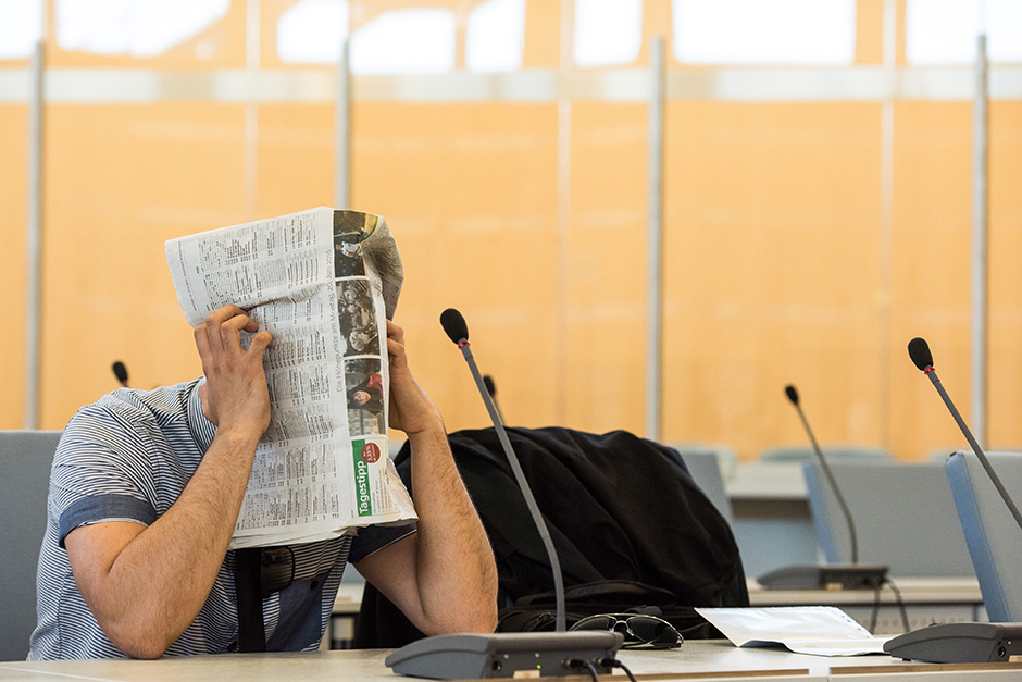 Defendant Shahid S hides his face behind a newspaper as he sits in a courtroom of the higher regional court in Duesseldorf, Germany. The man is accused of joining Islamist terror groups Jund al-Sham and the so-called Islamic State (IS).