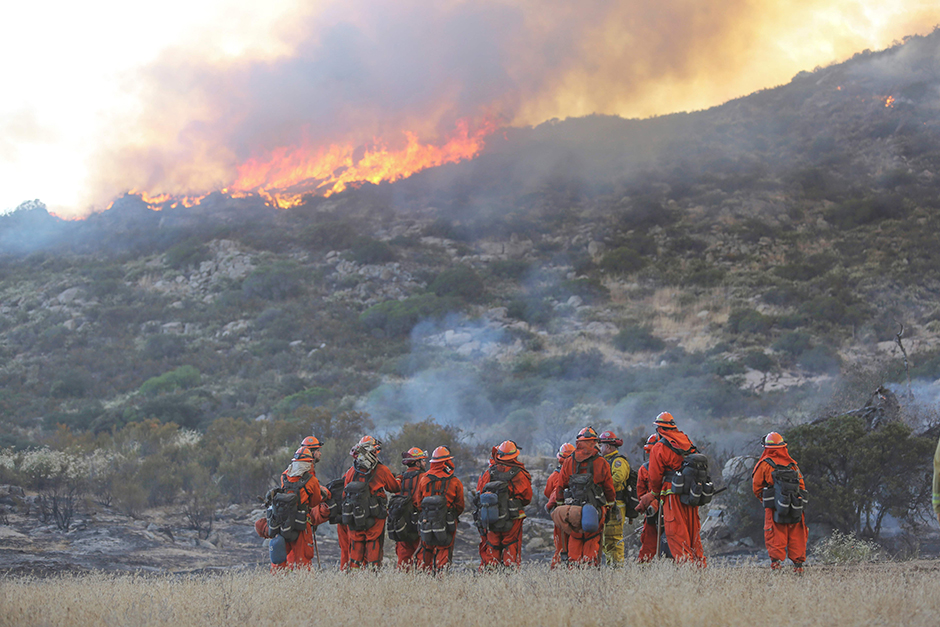 Firefighters are briefed on their duties as a backfire burns at the 6,500-acre Border Fire in eastern San Diego County, California.