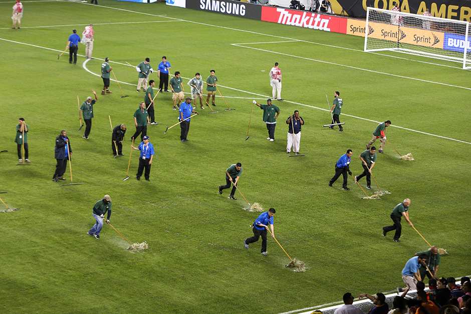 Workers mop the field during the half time of a Copa America Centenario semifinal football match between Chile and Colombia, as the beginning of the second half was delayed due to weather conditions in Chicago, Illinois, United States.