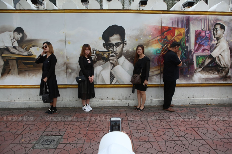 Mourners pay respect and pose for photos with the paintings of King Bhumibol on the wall of Silpakorn University near the Grand Palace.