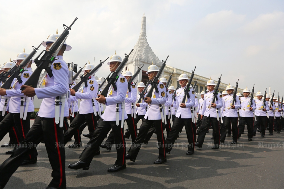 Soldiers march near the Grand Palace where mourners gather.