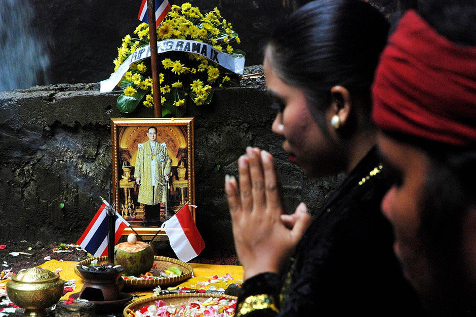 An image of late King Bhumibol is seen as Indonesian dancers perform an honour ritual and pray at Curug Dago, in Bandung, West Java province, on Oct 20.