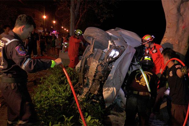 Police and rescue workers retrieve the dead and injured from a Mazda car after it crashed into a tree on Sunthornvichit Road along the Mekong River in Muang district of Nakhon Phanom early Saturday. Two people, including the driver, were killed and another one seriously hurt. (Photo by Pattanapong Sripiachai)
