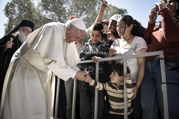 A boy shakes the hand of Pope Francis as he greets migrants and refugees at the Moria refugee camp on the Greek island of Lesbos on Saturday. (Reuters Photo)