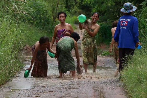 Villagers bathe on potholed road in protest