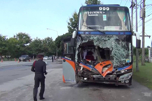 A police officer inspects the crash scene in which an elephant was killed after being hit by this inter-provincial bus in Hang Chat district, Lampang on Friday night