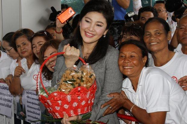 Former Prime Minister Yingluck Shinawatra is greeted by her as she arrives at the Supreme Court for a witness hearing in the rice-pledge scheme on Oct 7, 2016. (Photo by Tawatchai Kemgumnerd)