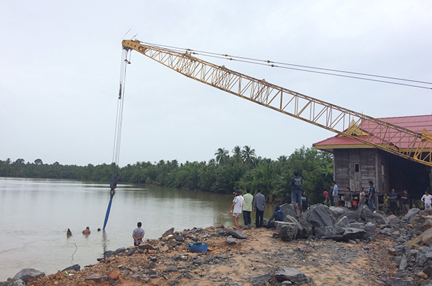 Backhoe vanishes into river as land subsides