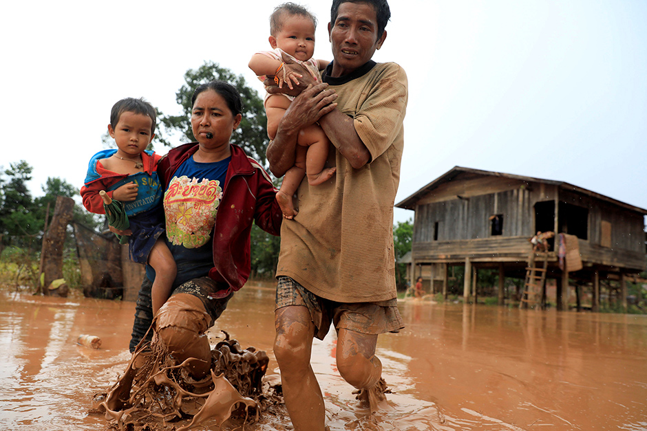 Parents carry their children as they leave their home during the flood on Thursday.