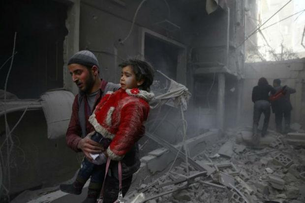 A man holds a child after an airstrike in the besieged town of Douma Eastern Ghouta Damascus Syria on Wednesday