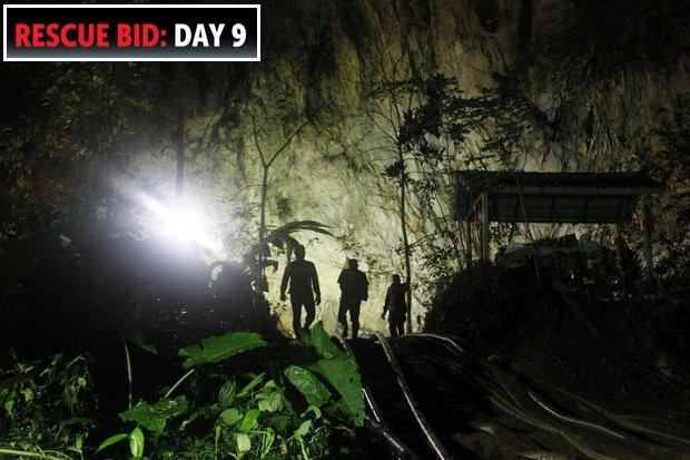 Rescue team members enter the Tham Luang cave on Sunday. The team got a break when the rains stopped and the pumps began making progress