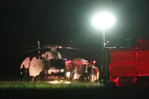 An emergency team rushes to the last helicopter carrying the final member of the Wild Boars football team to safety Tuesday night. (AP photo)