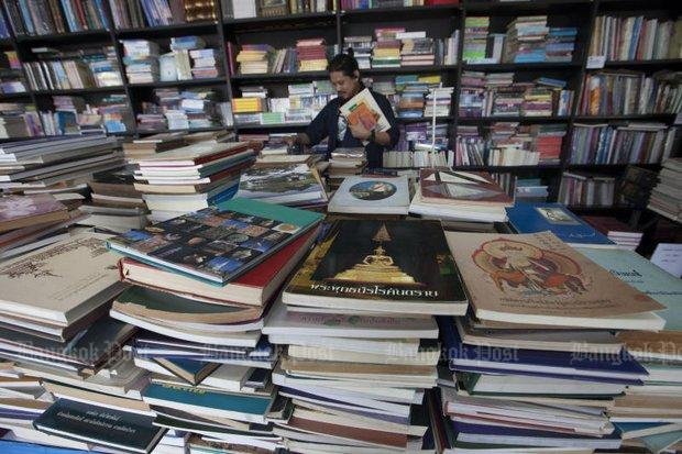 A Customer Selects From The Piles Of Titles At Second Hand Book Expo Rimkhobfa Bookstore Near Democracy Monument On Ratchadamnoen Klang Avenue