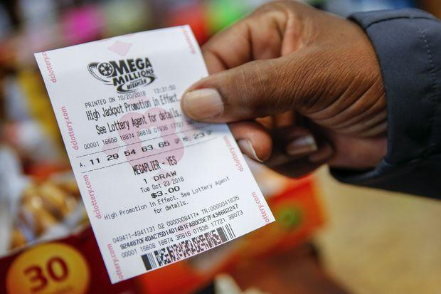 A customer shows his purchased Mega Millions lottery ticket at a retailer in Washington DC on Sunday